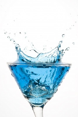 Blue drink splashing out of a martini glass